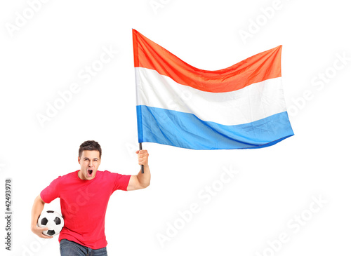 An euphoric fan holding a ball and waving a dutch flag