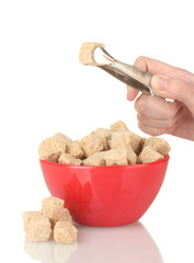 brown cane sugar cubes in bowl and womans hand holding