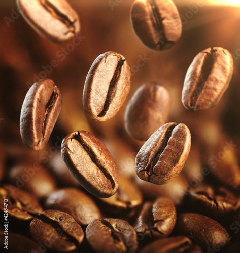 Fragrant fried coffe beans with focus on one are falling
