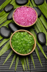 red and green bath salt in bowl with green palm on mat