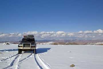 Car going over mountain pass in snow, Mongolia