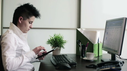 Young punk businesswoman with tablet computer in the office