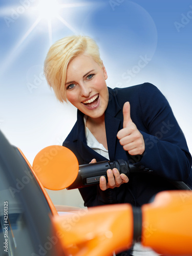 Woman has fun to load electrically powered car outdoors