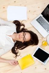 frau liegt zwischen unterlagen und laptop