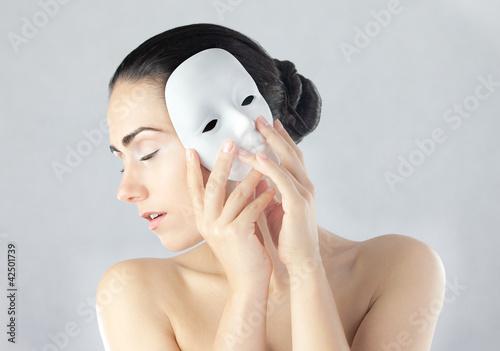Młoda kobieta trzymająca maskę obok twarzy