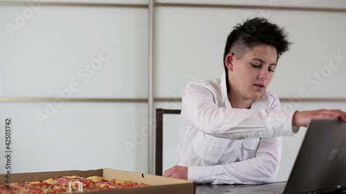 Young punk businesswoman eating pizza in the office, steadicam