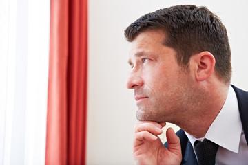 Geschäftsmann schaut nachdenklich aus Fenster