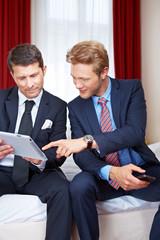 Geschäftsleute schauen auf Tablet Computer