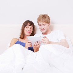 Paar im Bett schaut Video auf Tablet Computer