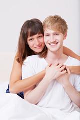 Junges Paar lacht im Bett