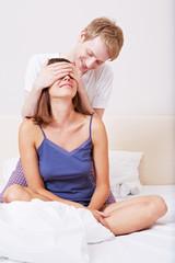 Mann hält Frau im Bett Augen zu