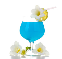 glass of blue cocktail with lime and flowers isolated on white