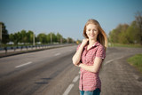 Young smiling blond female standing near the road