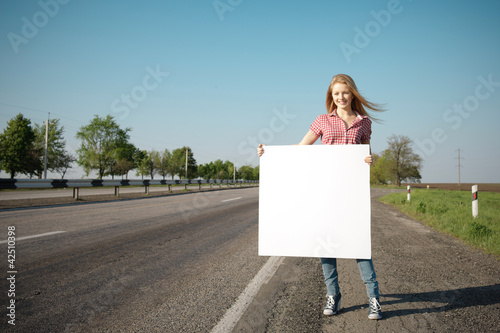 Full length offemale standing near road with blank whiteboard