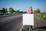 Full length of female standing near road with blank whiteboard