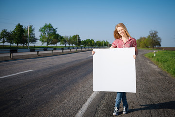Full length of female standing near road wirh blank whiteboard