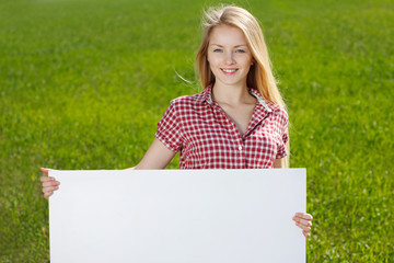 Young woman holding blank whiteboard, on grass background