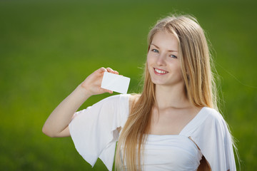 Young girl holding a blank credit card outdoor
