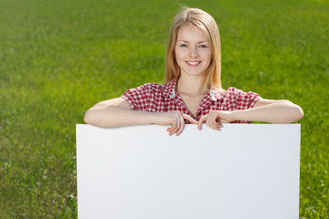 Smiling woman holding blank whiteboard
