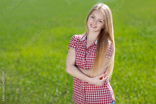 Beautiful girl standing with folded hands over grass background