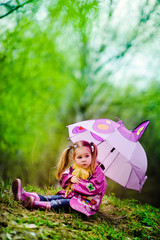 pretty little girl with umbrella in the park
