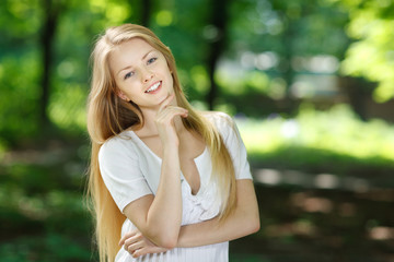 Smiling girl standing with folded hands over summer background