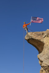Climber waves a flag the summit.