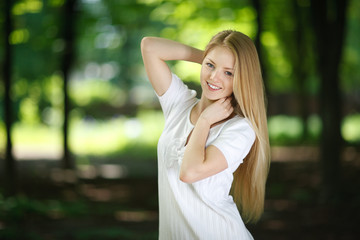 Beautiful smiling girl posing over green summer background