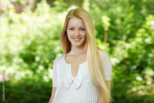 Closeup of young smiling woman on background of summer nature
