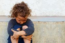 Biedny, smutny Dziewczynka dziecko siedzi przed betonowym murem