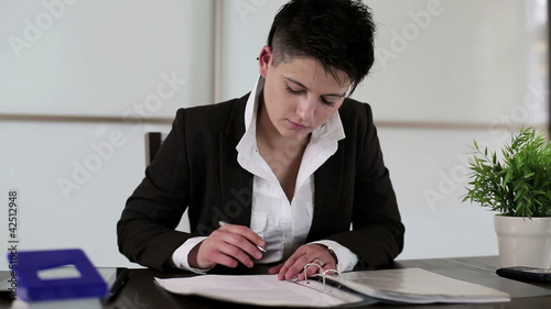 Young punk businesswoman signing documents in the office