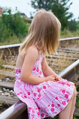 The girl is sitting on the railroad