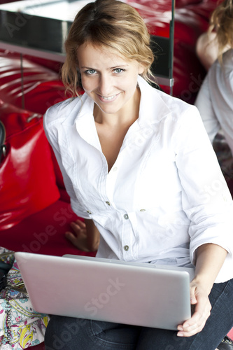 Happy young beautiful woman with laptop - indoors