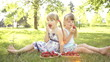 Happy girls eating strawberries. Sitting on the grass.