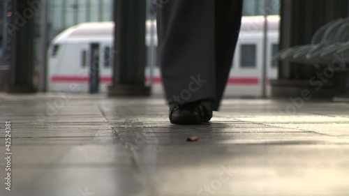 Female foots on Platform. Train on background.