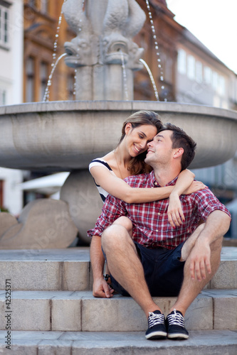 Affectionate young couple sitting by the fountain
