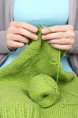 woman knitting green threads closeup