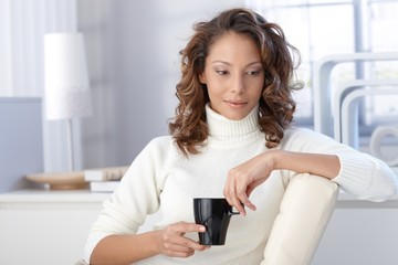 Ethnic woman drinking coffee at home