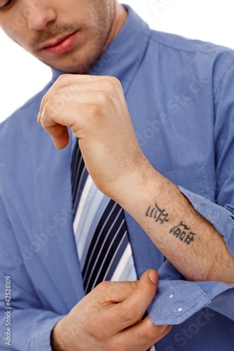 Young man showing tattoo in forearm