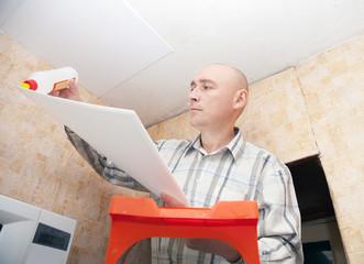 guy glues ceiling tile