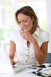 Woman in office talking on the phone with handfree device