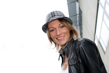 Portrait of woman with hat and leather jacket in town
