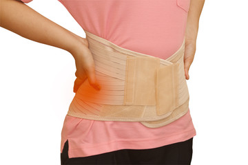 Woman in pain from back injury wearing lumbar brace corset