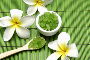 frangipani and Green salt in wooden spoon with bowl on green mat