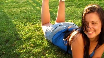Young brunette girl lying on fresh grass