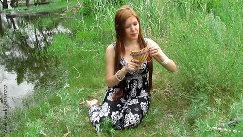 redhead girl reading playing flute outdoors full body