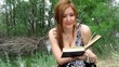 redhead girl with long hairs reading book outside