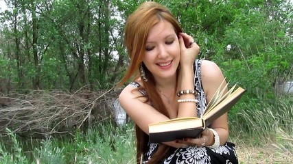 redhead girl reading book outdoors