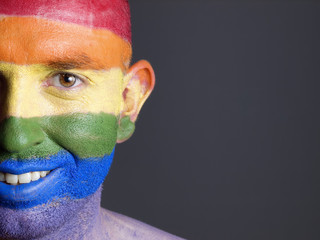 Gay flag painted on the face of a smiling man.