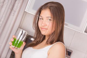 Молодая девушка с длинными волосами, завтракает на кухне